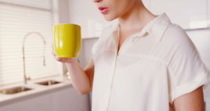 Woman using mobile phone and laptop while having coffee in kitchen stock footage