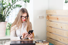 Woman using mobile phone and laptop at home. Stock Photo