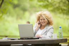 Woman using mobile phone and laptop in open office Stock Photography
