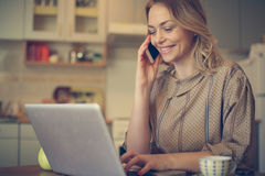 Woman using mobile phone and laptop. Stock Images