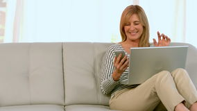 Woman using mobile phone and laptop stock video