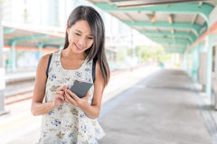 Woman using mobile phone in light rail station. Asian young woman Stock Image