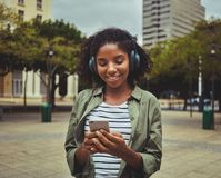 Woman using mobile phone while listening music on headphone stock images