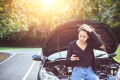 Woman using mobile phone while looking at broken down car on road. Woman using mobile phone while looking at broken down car on the road stock photos