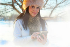 Woman using mobile phone and looking at you in a winter scene Royalty Free Stock Photo