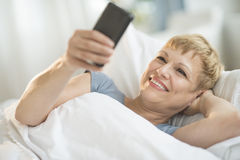 Woman Using Mobile Phone While Lying In Bed Stock Photos