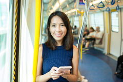 Woman using mobile phone in metro compartment Stock Images