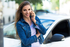 Woman using mobile phone near car Royalty Free Stock Images