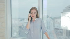 Woman using mobile phone at the office, standing in front of office windows. 4K stock video footage
