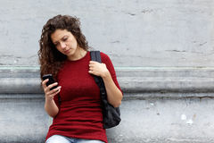 Woman using mobile phone outdoors looking serious Stock Images