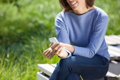 Woman using mobile phone in the park Royalty Free Stock Image