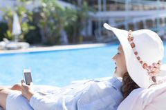Woman using mobile phone by the pool. Woman sitting in chair by the swimming pool and using smartphone stock image