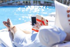 Woman using mobile phone by the pool. Woman sitting in chair by the swimming pool and using smartphone stock photography
