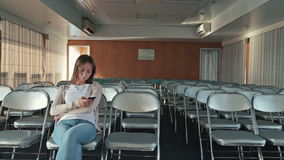 Woman using the mobile phone. Pretty caucasian woman looking around and using the smart phone in the empty conference hall of cruise ship. Sunrise time stock footage