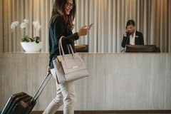 Business traveler in hotel hallway with phone. Woman using mobile phone and pulling her suitcase in a hotel lobby. Female business traveler walking in hotel Royalty Free Stock Image