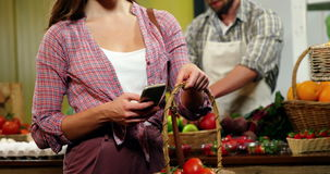 Woman using mobile phone while purchasing tomatoes stock footage