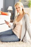 Woman Using Mobile Phone Relaxing Sitting On Rug Stock Photography