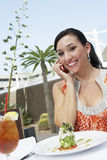 Woman Using Mobile Phone In Restaurant Royalty Free Stock Photo