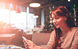 Woman using a mobile phone in restaurant, cafe,bar Royalty Free Stock Photography