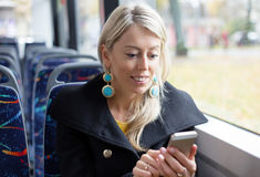 Woman using mobile phone while riding in public transport Stock Photo
