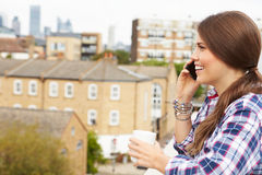 Woman Using Mobile Phone On Rooftop Garden Drinking Coffee Royalty Free Stock Photography