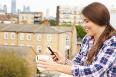 Woman Using Mobile Phone On Rooftop Garden Drinking Coffee Royalty Free Stock Photo