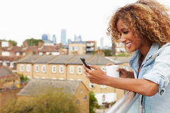 Woman Using Mobile Phone On Rooftop Garden Drinking Coffee Stock Image