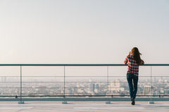 Woman using mobile phone at rooftop during sunset with copy space, communication or lonely people concept.  royalty free stock photo