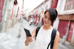 Woman using mobile phone in Rua da felicidade Royalty Free Stock Images