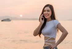 Woman using mobile phone on the sea beach with sunset. Beautiful woman using mobile phone on the sea beach with sunset Stock Photography