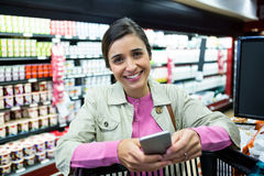 Woman using mobile phone while shopping Stock Image