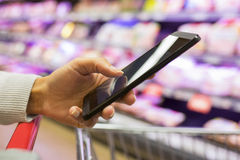 Woman using mobile phone while shopping in supermarket Royalty Free Stock Images