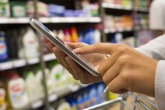 Woman using mobile phone while shopping in supermarket Stock Photos