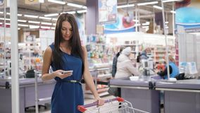 Woman using mobile phone while shopping in supermarket, trolley mall grocery shop store. Woman using mobile phone while shopping in supermarket, trolley stock footage