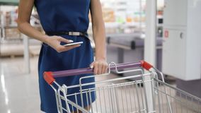 Woman using mobile phone while shopping in supermarket, trolley mall grocery shop store. Woman using mobile phone while shopping in supermarket, trolley stock video