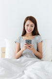 Woman using mobile phone and sitting on bed Stock Photography