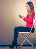 Woman using mobile phone sitting in chair. Stock Photos