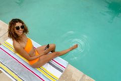 Woman using mobile phone while sitting at the edge of swimming pool. High angle view of happy mixed-race woman using mobile phone while sitting at the edge of royalty free stock image