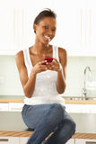 Woman Using Mobile Phone Sitting In Modern Kitchen Stock Photo