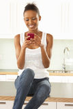 Woman Using Mobile Phone Sitting In Modern Kitchen Stock Photography