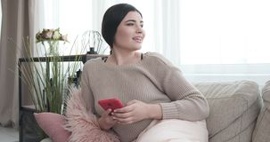 Woman using mobile phone on sofa at home. Thoughtful woman text messaging on mobile phone at home stock video footage