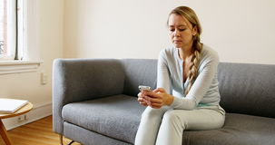 Woman using mobile phone on sofa in living room stock video
