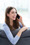 Woman using mobile phone on sofa Royalty Free Stock Photos