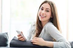 Woman using mobile phone on sofa Stock Image