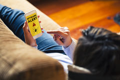 Woman using a mobile phone with a spyware alert in the screen. Spyware alert notification in a mobile phone held by woman while lying on the sofa at home stock photos