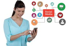 Woman using mobile phone while standing by social media diagram against white background. Digital composite of Woman using mobile phone while standing by social Stock Photos