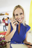 Woman Using Mobile Phone In Store Stock Photos