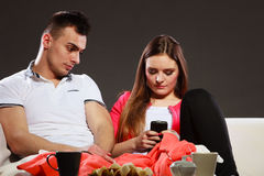 Woman using mobile phone texting and bored man. Stock Image
