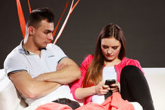 Woman using mobile phone texting and bored man. Royalty Free Stock Photos