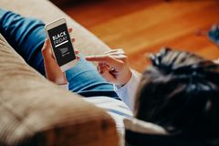 Black Friday banner in a mobile phone screen while woman holds it lying down at home Stock Photos